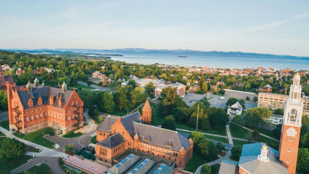 An aerial view of the UVM campus, home to the Gund Institute for Environment, in Burlington, Vermont, Lake Champlain, and the Adirondack mountains.