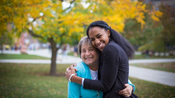 uvm staff member hugging student worker in front of yellow foliage