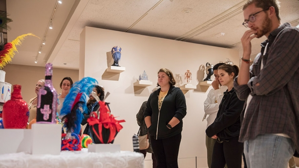 A group of community members take in the Vodou altar featured in the Spirited Things exhibition