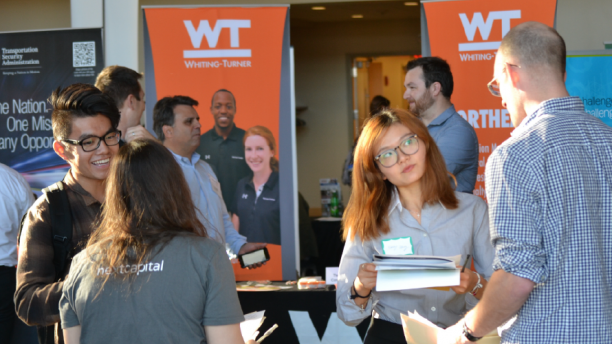 two students speaking with recruiters at a career fair