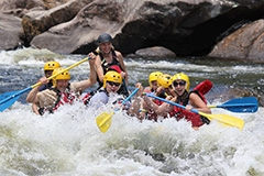 People in a raft in the rapids of a river