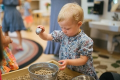 Toddler plays with natural materials at the Campus Children's School