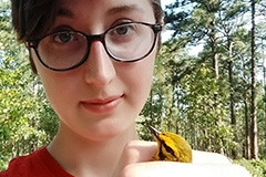 Student holding yellow bird