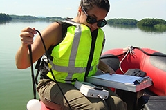 Student conducting water study in rubber raft