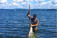 A student sets a net while standing in the lake