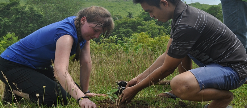 two students working in a field while on peace corps mission