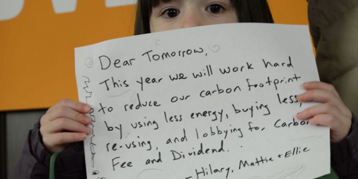 girl holding commitment to energy and carbon footprint reduction