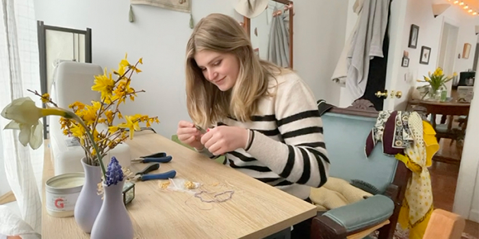 UVM student Ali Starkweather making jewelry on a table in her home.