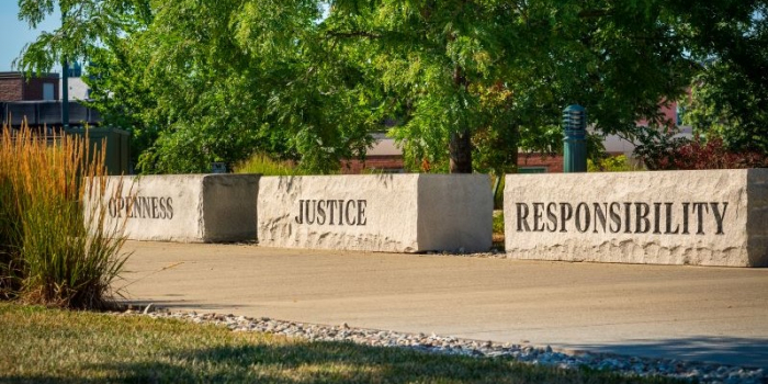 Three large stone benches along a walkway that are engraved with the words openness, justice, responsibility