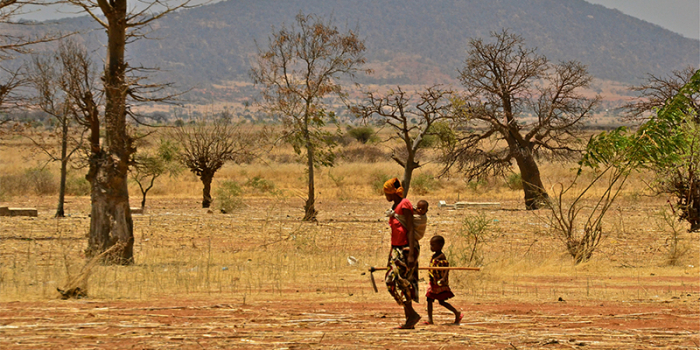 A farmer woman walks with her two children in a farming village outside Dodoma, Tanzania