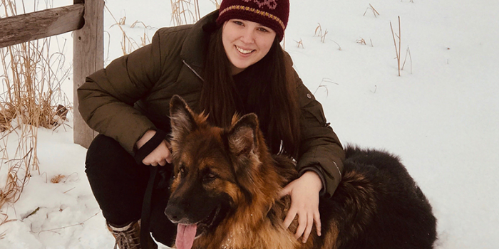 Julia Kitonis dressed for Winter with a snowy backdrop and german shepard type dog companion