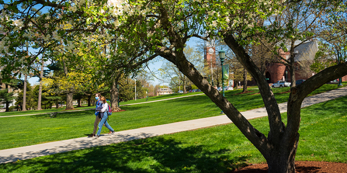 two students wearing masks walking on campus green