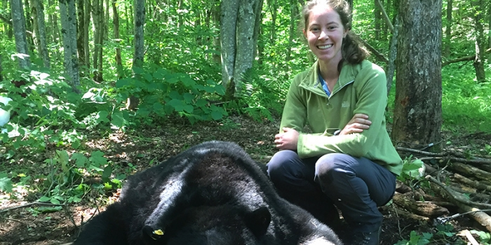 Student in woods with sedated black bear
