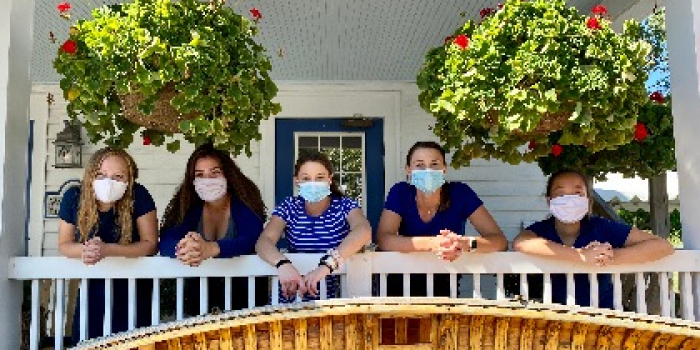A group of people on a balcony wearing face masks