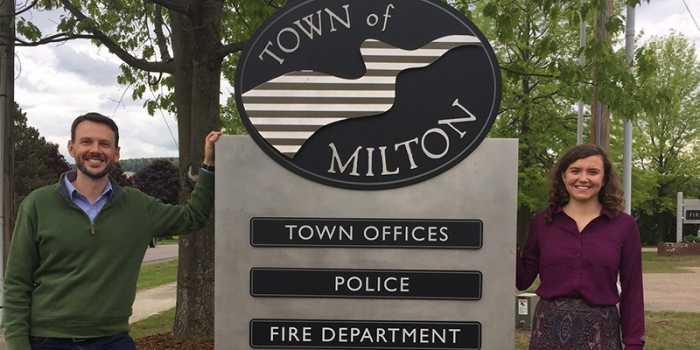 Student and town official stand next to Town of Milton sign