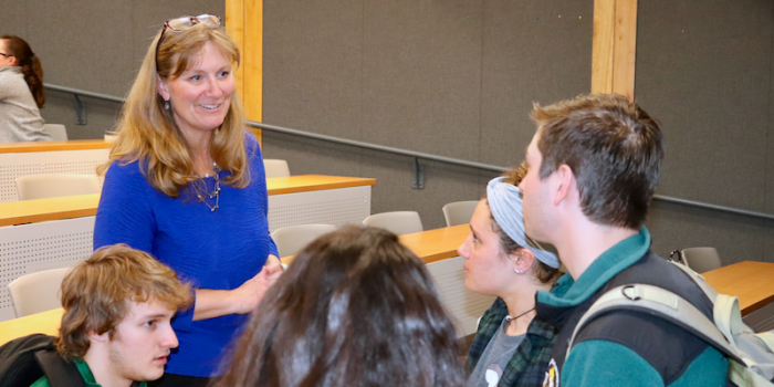 Haley Woodside-Jiron speaking with a group of students after class.