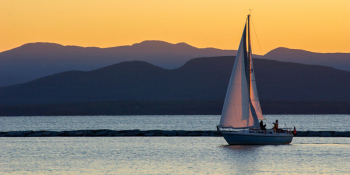 An image of a sailboat on Vermont's Lake Champlain at sunset. The visual appearance of Lake Champlain – specifically, how clean its water looks – has a major effect on the state economy, a new UVM study finds. The research was made possible with support f