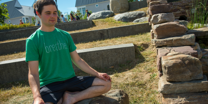 Student sitting peacefully outdoors with eyes closed, as in meditation.