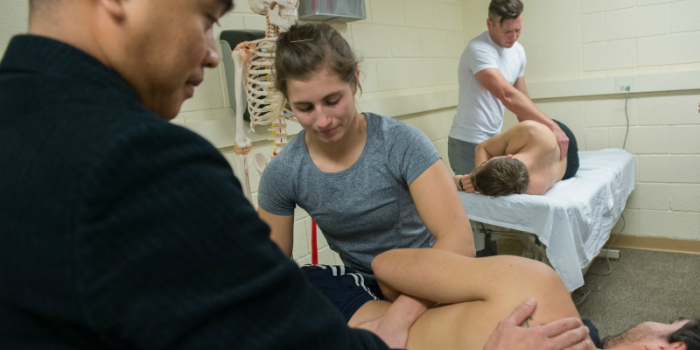 Professor Escorpizo working with students in physical therapy lab.
