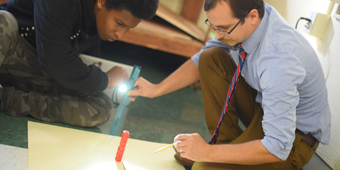 Teacher engages student in shadow experiment.