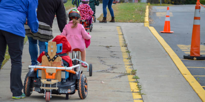 children on bikes and in an adapted car in a line