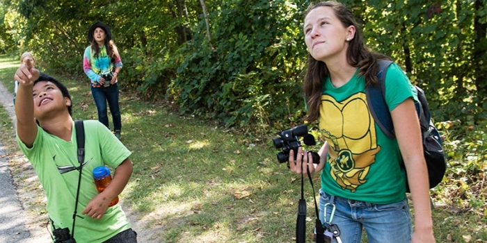 "Tobey, a fourth-grader at JJ Flynn Elementary School watches birds over the bike path in Burlington, VT, with his UVM mentor and ""bird buddy,"" Sara Fergus, a UVM sophomore enrolled in Environmental Studies 295, ""Birding to Change the World."""
