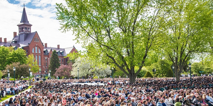 Graduates sit on the UVM Green in front of Old Mill