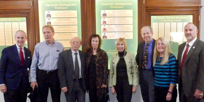 University leadership and Distinguished University Professors in front of the new faculty display.  Pictured from left are President Tom Sullivan; Mark T. Nelson, chairman and University Distinguished Professor of Pharmacology; Wolfgang Mieder, University