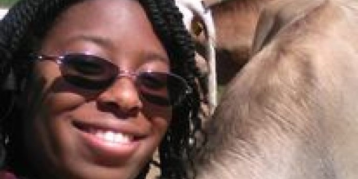 image description: a smiling young woman with sunglasses leaning against the neck of a brown cow on a sunny day