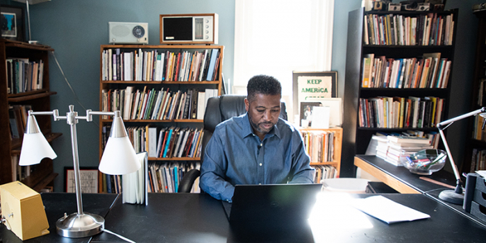 UVM professor of English Major Jackson writes at his computer in home office