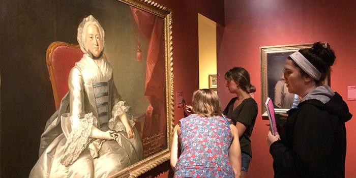 Three students examine a portrait in a museum