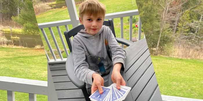 Boy holding playing cards.