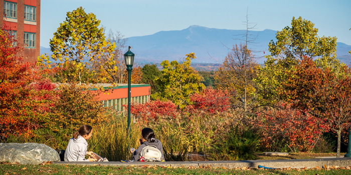 two students sit in outdoor amphitheater with Mount Mainsfield in the distance