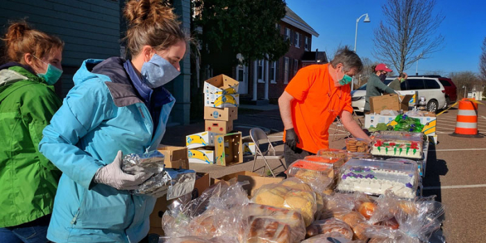 Volunteers at the Winooski Food Shelf follow new COVID-19 safety protocols and arrange a Saturday food pick-up program outdoors.