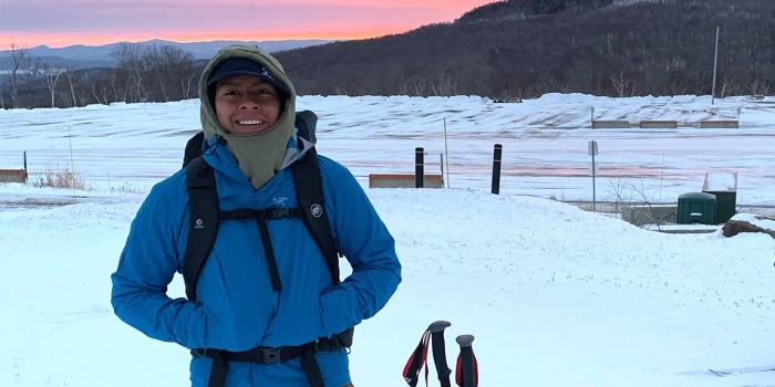 Andrew Romano stands in snow-covered, empty ski resort parking lot at sunrise