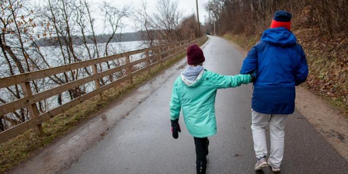 Child and parent walk along a bike path