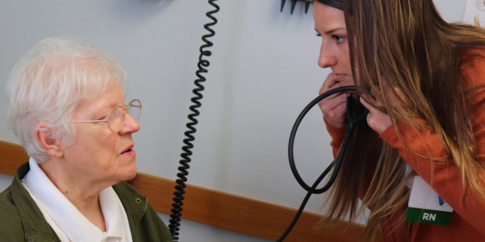 An older person sitting in an exam room in conversation with a young nurse who is wearing a stethoscope around her neck and looking intently at the patient.