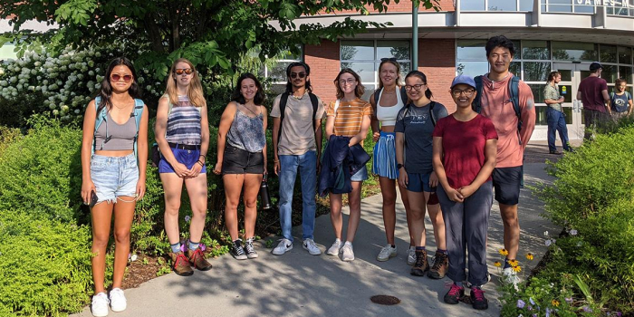 Eight undergraduate scholars and their leader in front of campus building