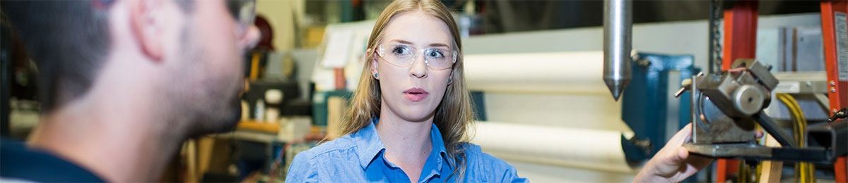 Woman wearing goggles working in a factory setting