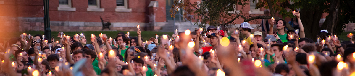 Students holding candles on main green
