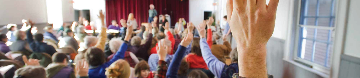 Header image of people raising their hands at a town meeting.