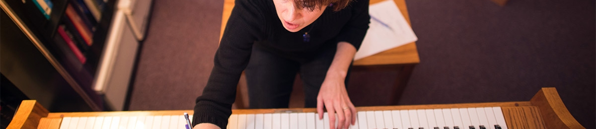 woman compusing music in front of piano