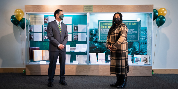 President Suresh Garimella and Vice President Wanda Heading-Grant stand in front of Celebrating Diverse Voices display case, distanced and masked
