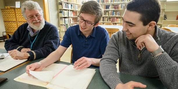 Steve Terry and students look at papers in UVM's Special Collections
