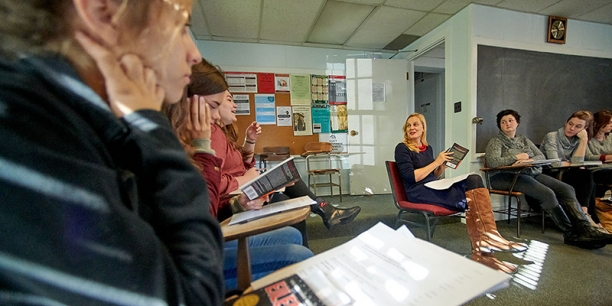Students sit at desks in a circle in a classroom around professor Maria Hummel