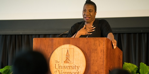 Tarana Burke speaks at a podium at the University of Vermont