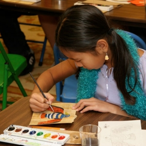 A young student completes an art activity on papyrus paper