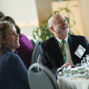 Man laughing, wearing black suit with a green tie. Sitting at a formally set luncheon table.