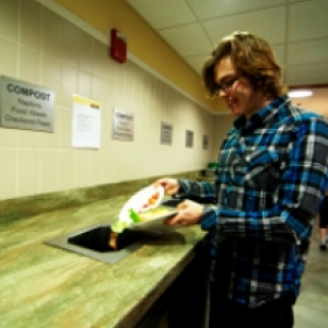 Student scraping plate of food