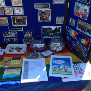 Resource table with rainbow flag and various flyers, buttons, and other materials